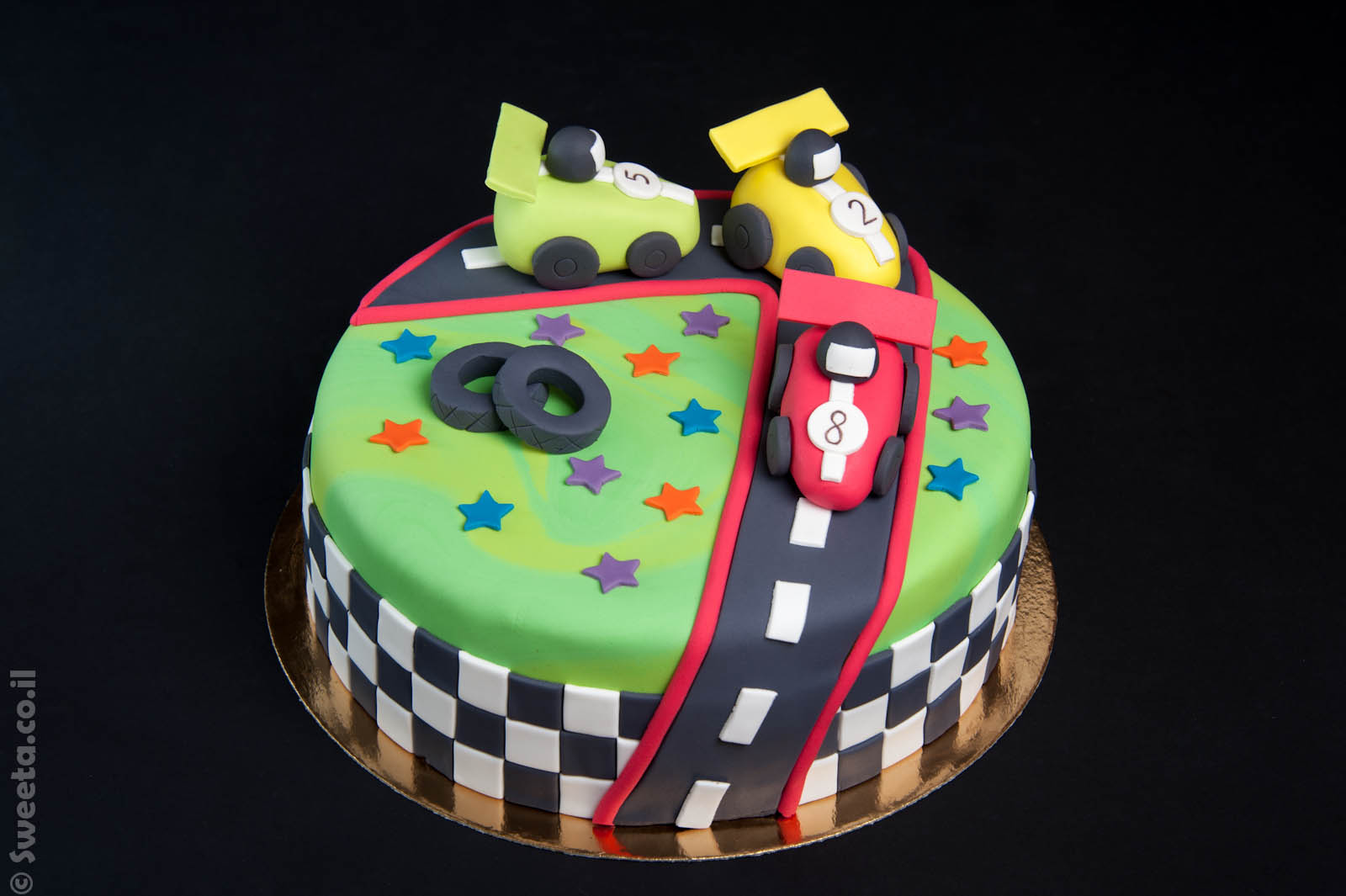 עוגת מכוניות מרוץ מעוצבות בבצק סוכר על מסלול
